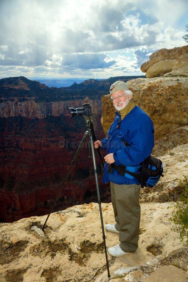 El hombre mayor se coloca en el borde del norte de Grand Canyon que toma el pi imagen de archivo libre de regalías