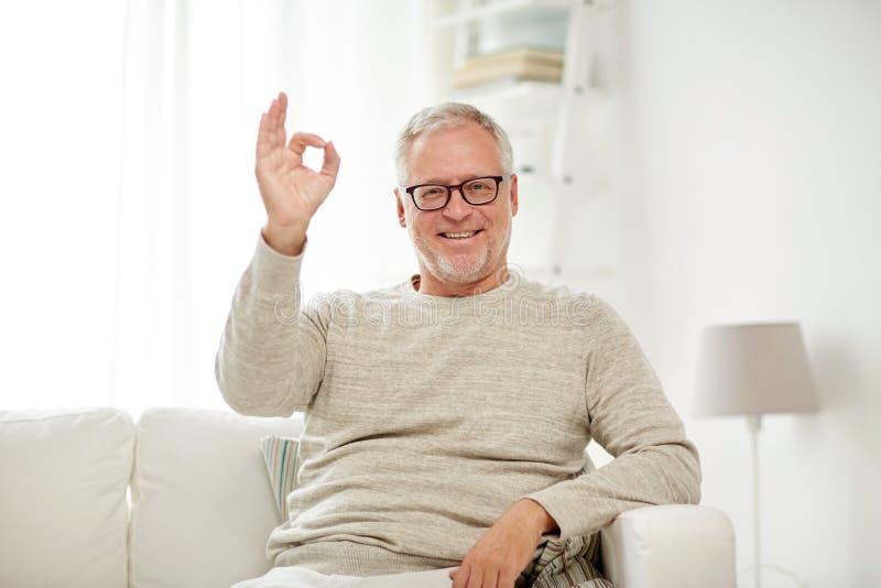 El hombre mayor sonriente que muestra la mano aceptable firma en casa imagen de archivo