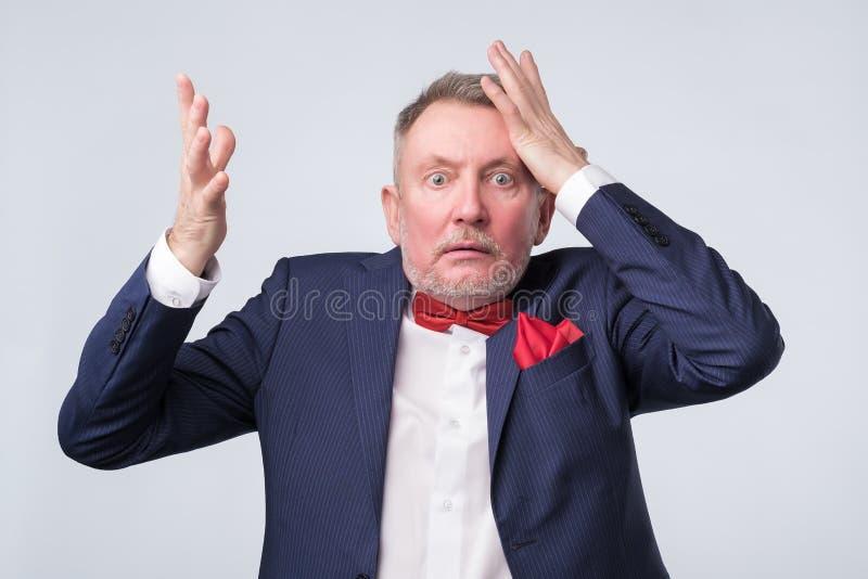 El hombre mayor sorprendido con la mano encendido va a error imagen de archivo libre de regalías