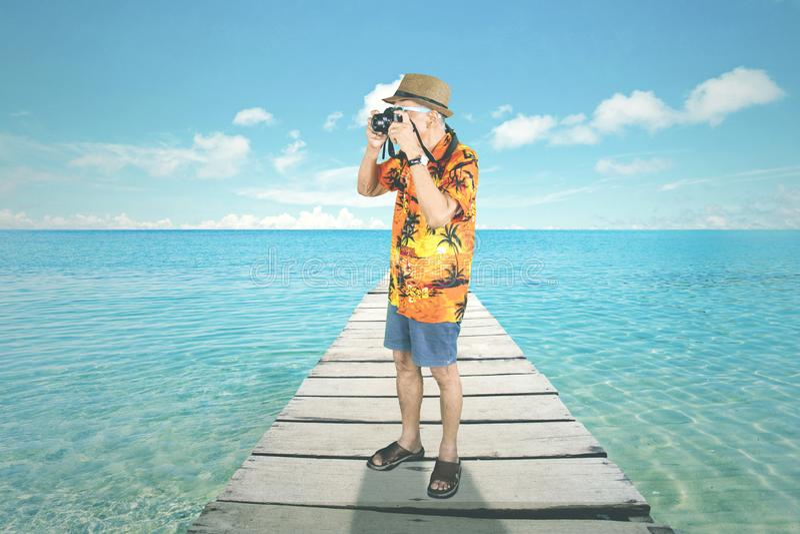 El hombre mayor toma una foto en la playa fotos de archivo libres de regalías