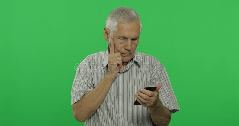 El hombre mayor trabaja en un smartphone Viejo hombre hermoso en el fondo dominante de la croma imágenes de archivo libres de regalías