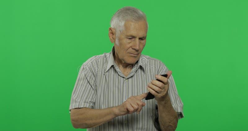 El hombre mayor trabaja en un smartphone Viejo hombre hermoso en el fondo dominante de la croma fotografía de archivo