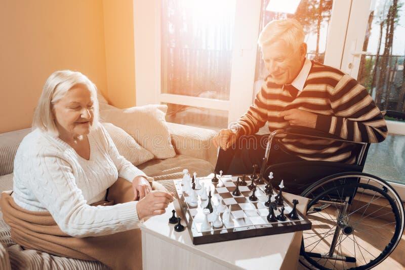 El hombre mayor y la mujer juegan a ajedrez en la clínica de reposo fotos de archivo libres de regalías