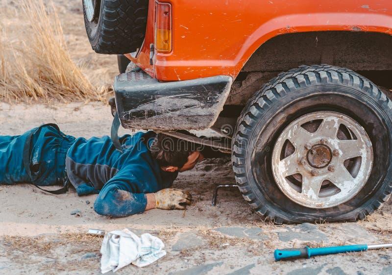 El hombre miente debajo de un coche 4x4 en un camino de tierra imágenes de archivo libres de regalías