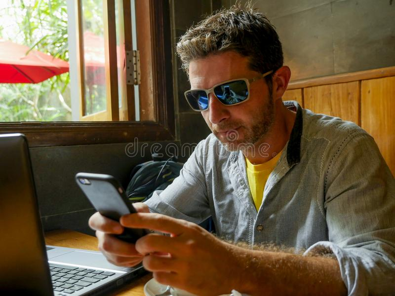El hombre milenario feliz y acertado atractivo joven que trabaja de cafetería de Internet con el ordenador portátil y el teléfono imagen de archivo