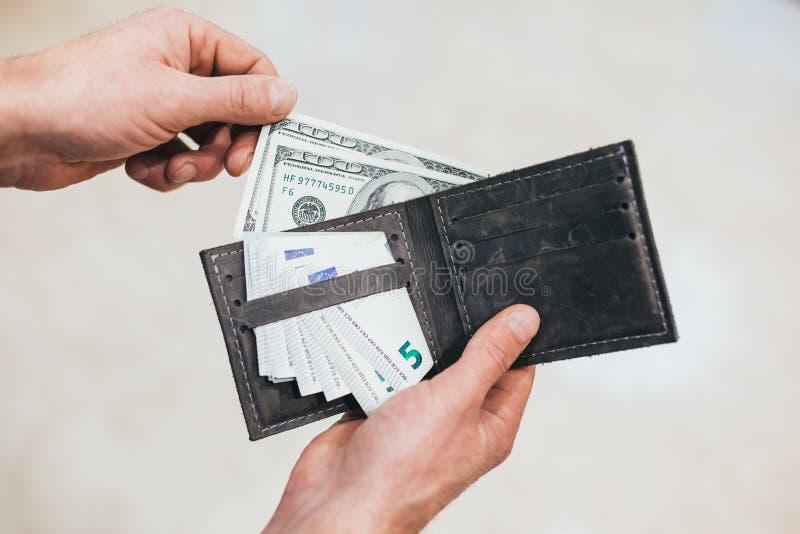 El hombre mira en la cartera efectivo Hombre rico que cuenta su dinero Cierre para arriba fotos de archivo