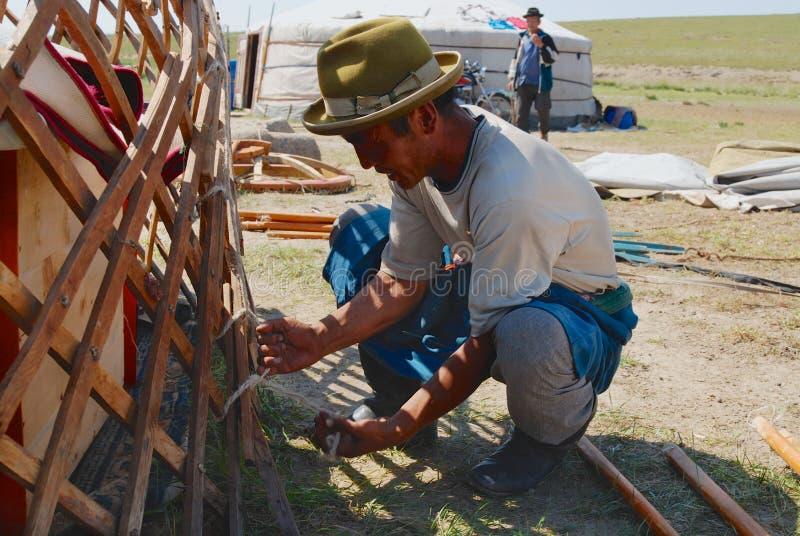 El hombre mongol monta el marco de madera de un yurt Ger o de la tienda nómada en estepa en Kharkhorin, Mongolia foto de archivo libre de regalías