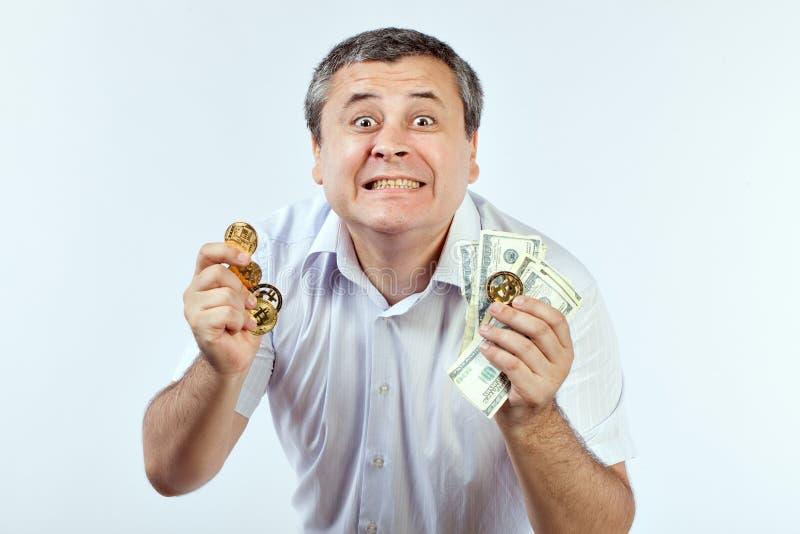 El hombre muestra bitcoins y dólares imagen de archivo