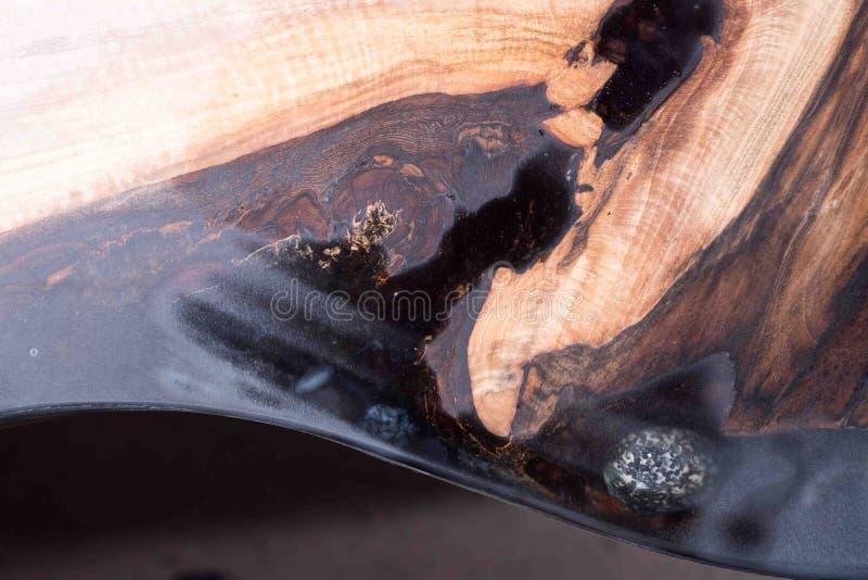 El hombre muestra a diferencia el árbol mojado y se seca resina negra con las piedras dentro foto de archivo
