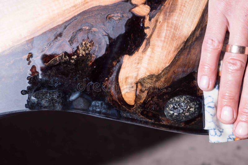 El hombre muestra a diferencia el árbol mojado y se seca resina negra con las piedras dentro foto de archivo libre de regalías