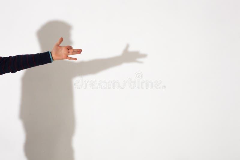 El hombre muestra la sombra del perro con los fingeres fotografía de archivo