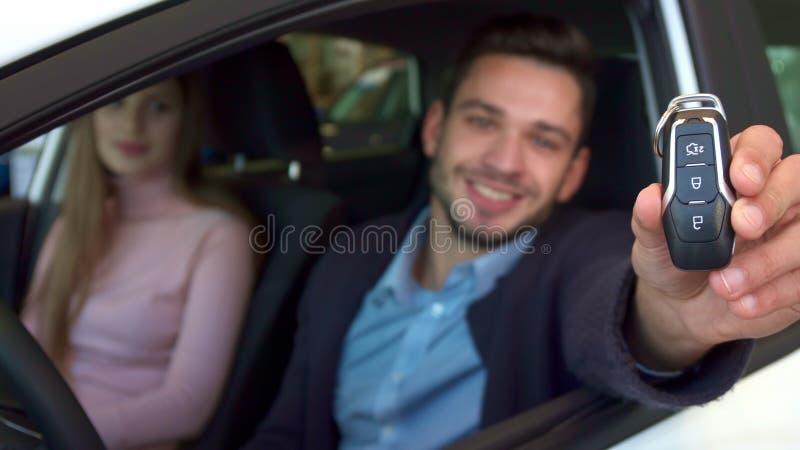 El hombre muestra llave a través de la ventanilla del coche foto de archivo