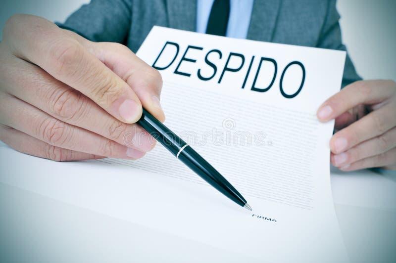 El hombre muestra un documento con el despido del texto, despido en español fotografía de archivo libre de regalías