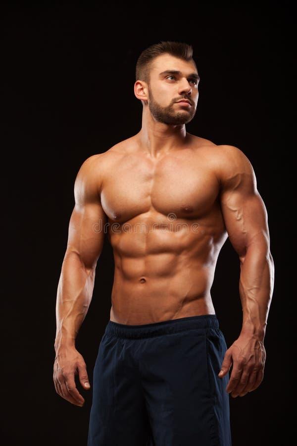 El hombre muscular de la aptitud es de presentación y que muestra de su torso con seis ABS del paquete Aislado en fondo negro con imágenes de archivo libres de regalías