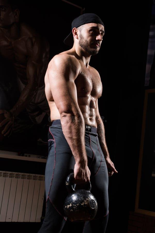 El hombre muscular en el gimnasio entrena con el kettlebell imagen de archivo libre de regalías