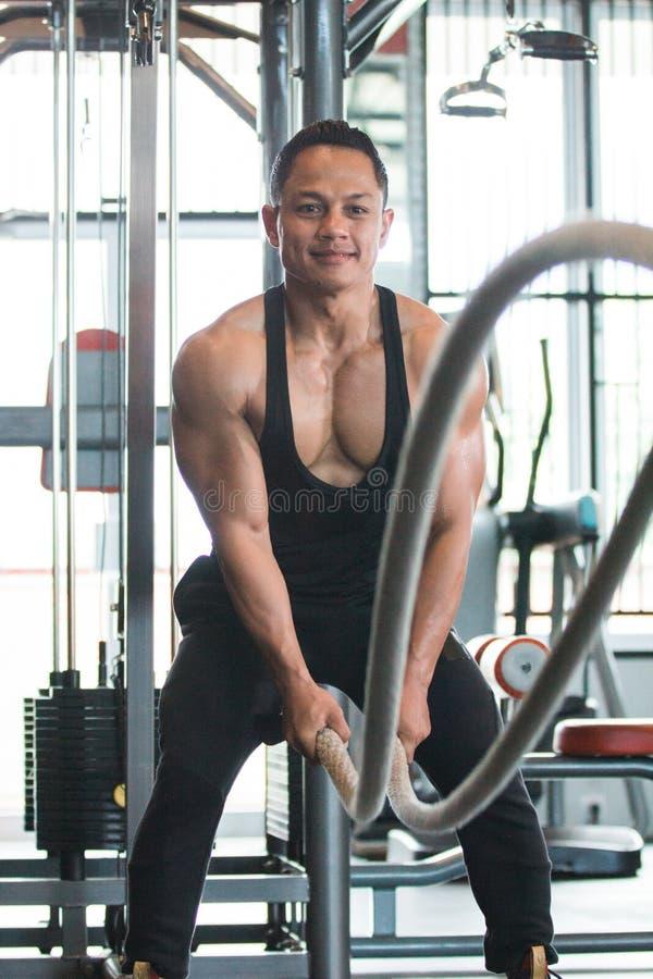 El hombre muscular está haciendo ejercicio de la cuerda de la batalla imagen de archivo libre de regalías