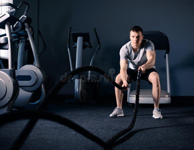 El hombre muscular está haciendo ejercicio de la cuerda de la batalla en gimnasio moderno de la aptitud CrossFit y concepto sano  fotografía de archivo libre de regalías