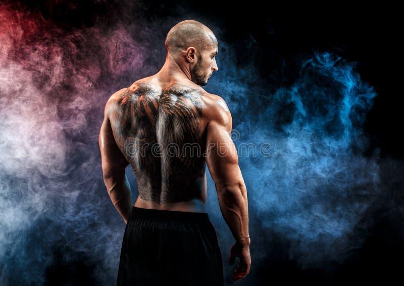 El hombre muscular irreconocible con el tatuaje encendido apoya contra de fondo negro Aislado imagenes de archivo