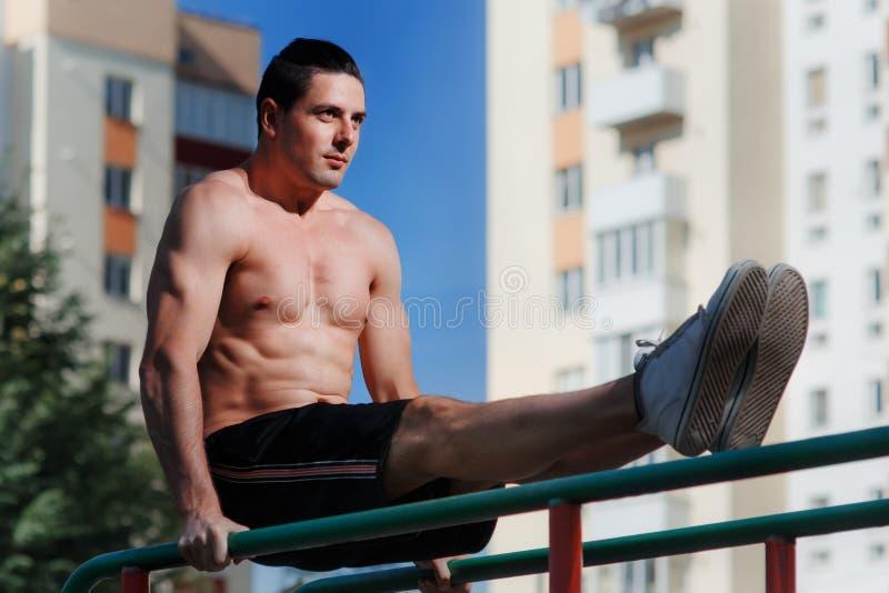 El hombre muscular joven de la estructura que hace tirón sube ejercicios en barra horizontal al aire libre fotos de archivo libres de regalías