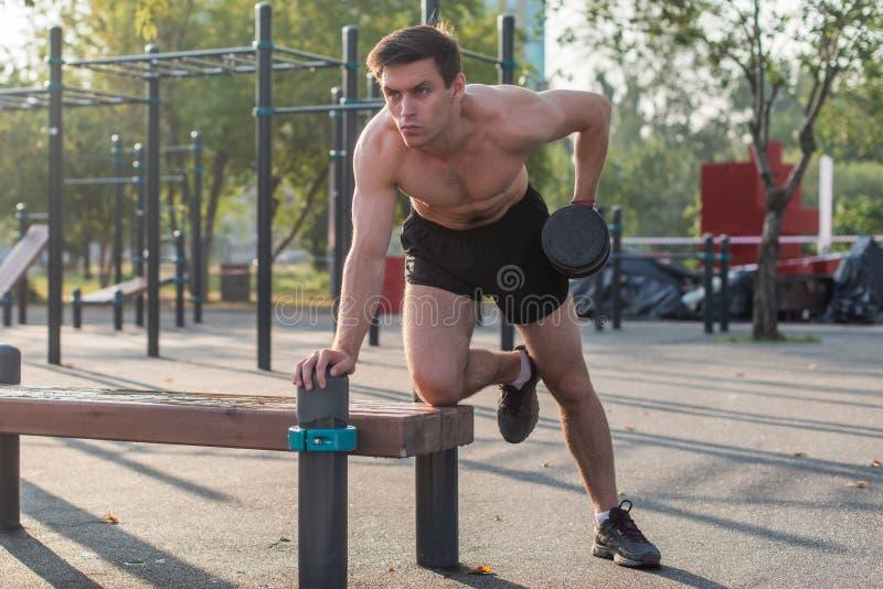 El hombre muscular levanta la pesa de gimnasia Ejercicio trasero Sola fila de la pesa de gimnasia del brazo imágenes de archivo libres de regalías