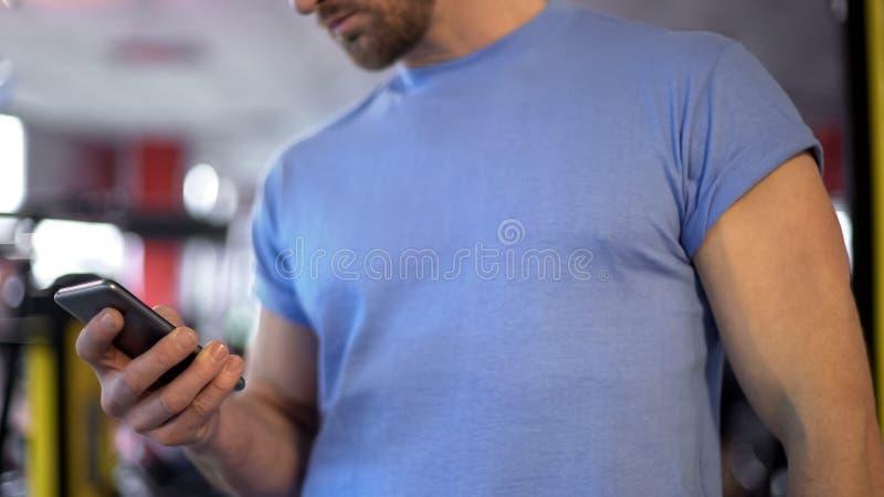 El hombre muscular que comprueba calorías de la quemadura asciende en su aptitud app en smartphone imagen de archivo libre de regalías