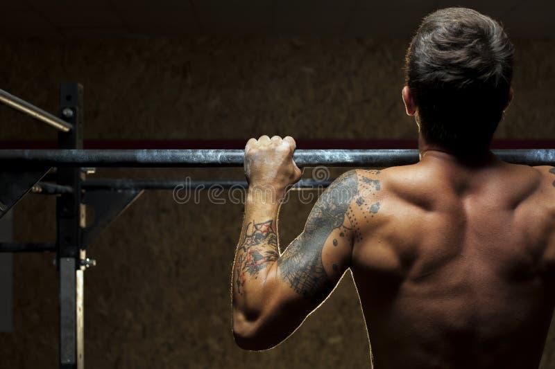 El hombre muscular que hace tirón sube ejercicio en gimnasio imagen de archivo