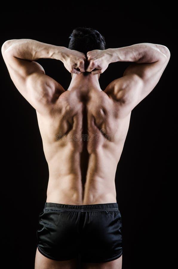 El hombre muscular que presenta en estudio oscuro fotografía de archivo