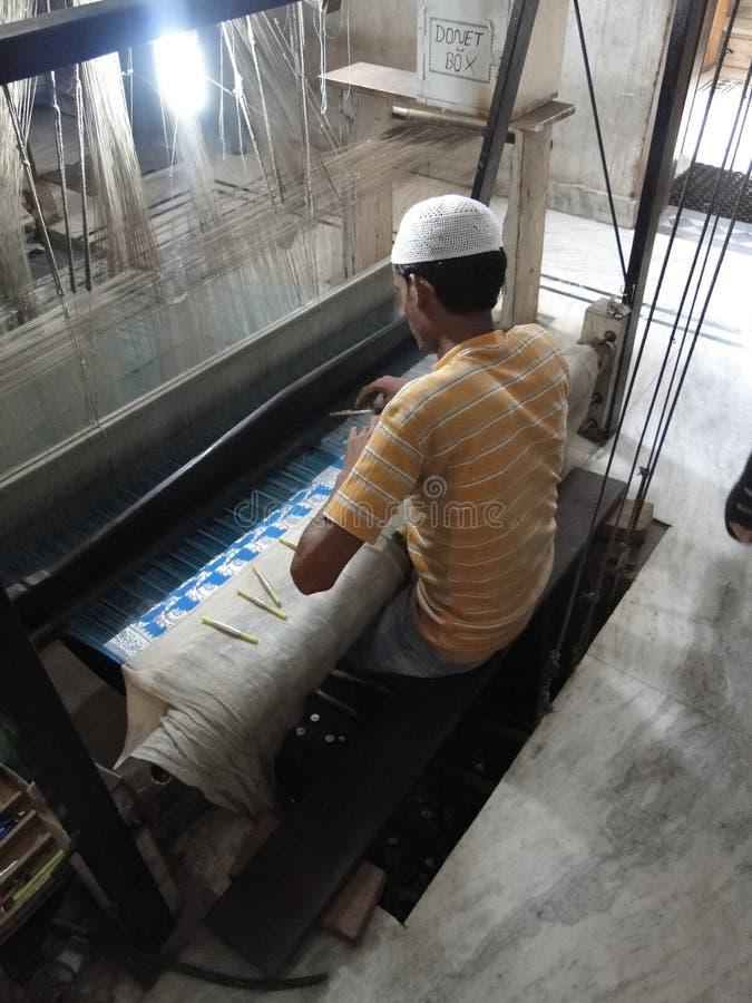 El hombre musulmán joven funciona con un telar para tejer el brocado de seda imagenes de archivo