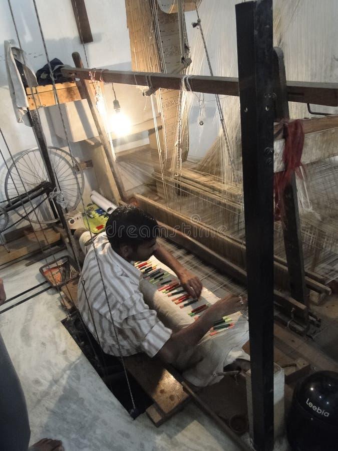El hombre musulmán joven funciona con un telar para tejer el brocado de seda foto de archivo libre de regalías