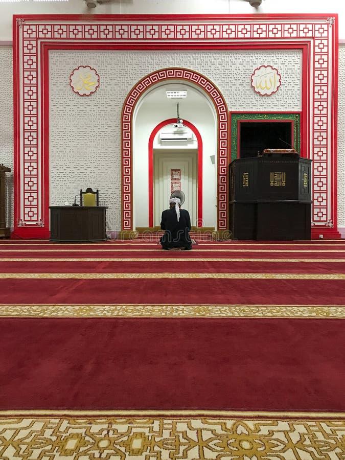 El hombre musulmán no identificado adentro se sienta en la posición Masjid Muhammadiah, Ipoh, Perak del solat foto de archivo