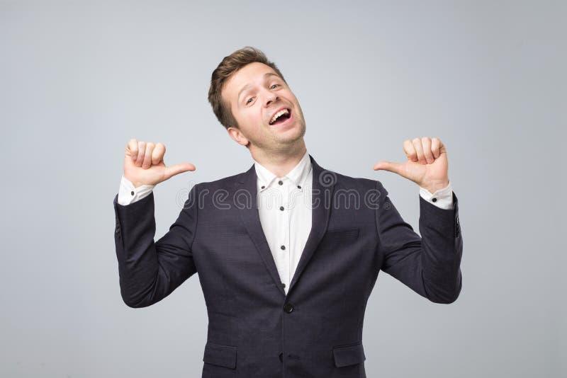 El hombre muy orgulloso muestra a sus fingeres en sí mismo el standong aislado en fondo lgray foto de archivo