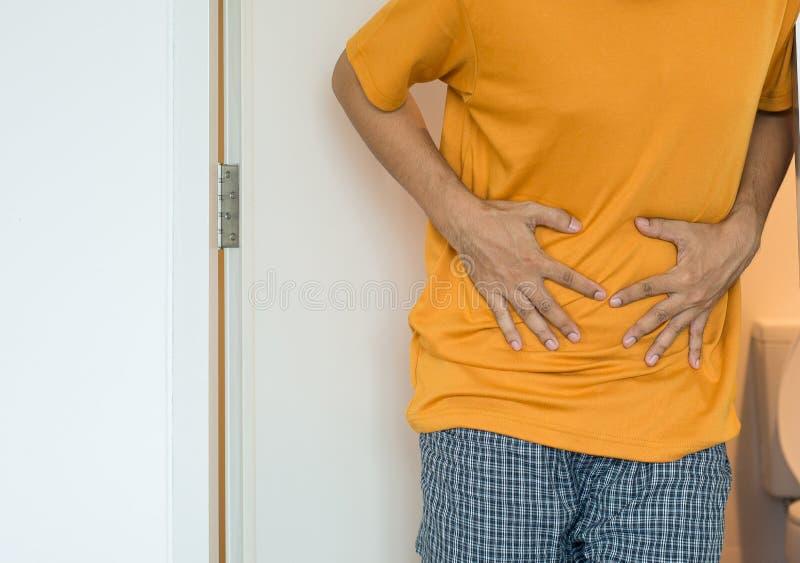 El hombre necesita utilizado el retrete y sufre de diarrea y los hemorroides despiertan después por mañana en la casa imagen de archivo libre de regalías