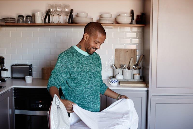El hombre negro americano atractivo está planchando la camisa blanca en casa fotografía de archivo