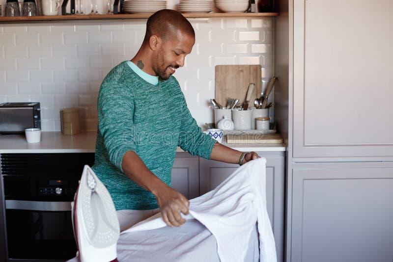 El hombre negro americano atractivo está planchando la camisa blanca en casa foto de archivo