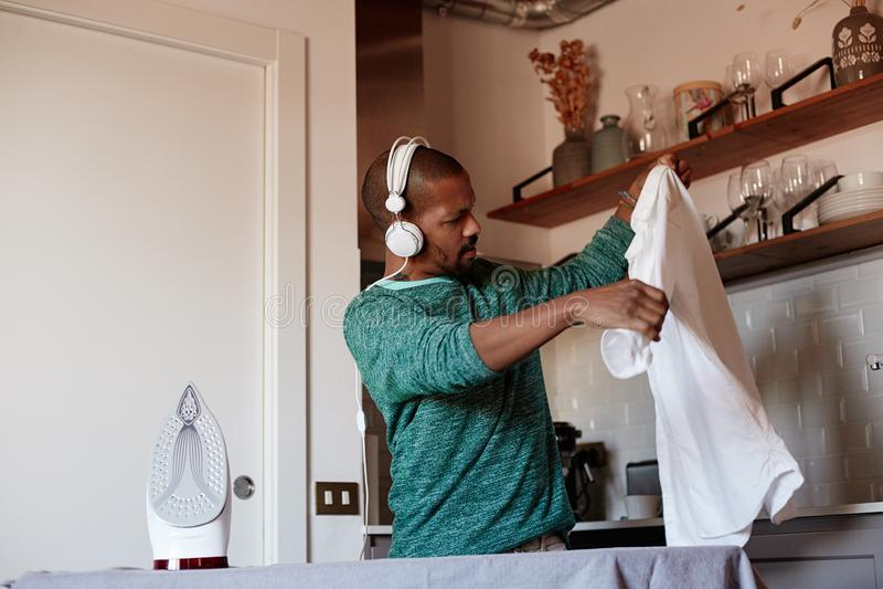 El hombre negro americano atractivo está planchando la camisa blanca en casa imagenes de archivo