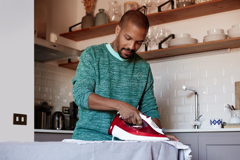 El hombre negro americano atractivo está planchando la camisa blanca en casa fotos de archivo