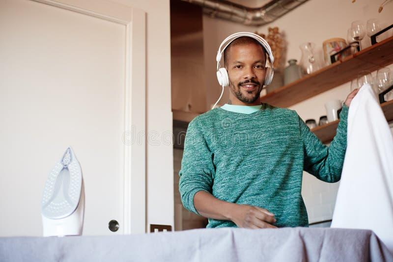 El hombre negro americano atractivo está planchando la camisa blanca en casa foto de archivo libre de regalías