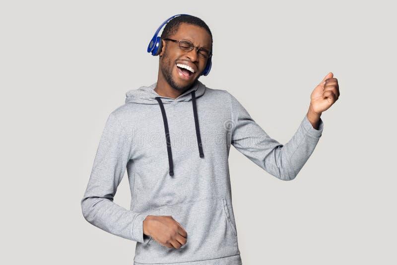 El hombre negro emocionado en auriculares se divierte que disfruta de música fotografía de archivo libre de regalías