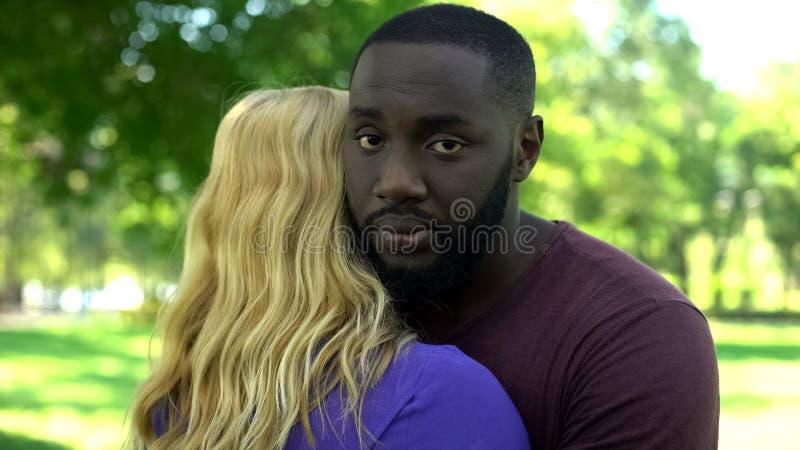El hombre negro triste abraza a la mujer querida, choque de intereses, malentendido fotografía de archivo libre de regalías