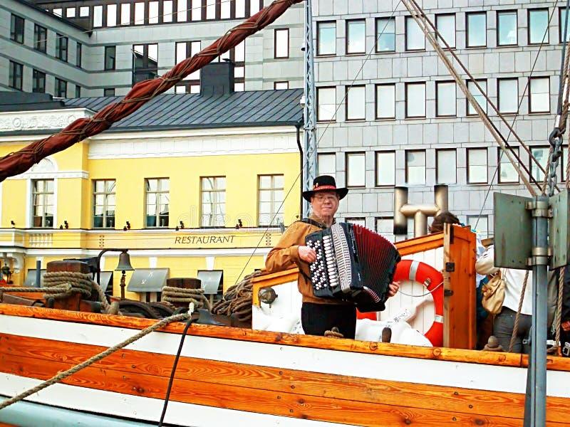 El hombre no identificado juega el acordeón en un terraplén en Helsinki, Finlandia fotos de archivo libres de regalías