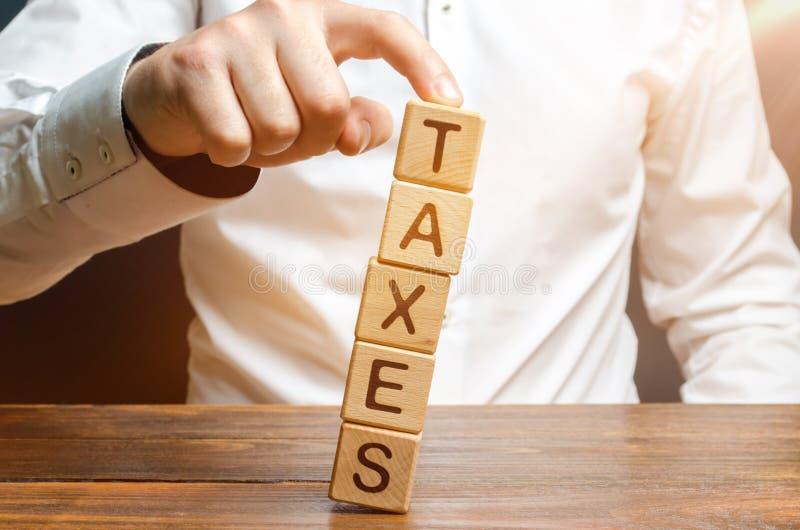El hombre no permite que la torre caiga del libro con los impuestos de la palabra Presi?n fiscal pesada, reduciendo la carga en n fotografía de archivo