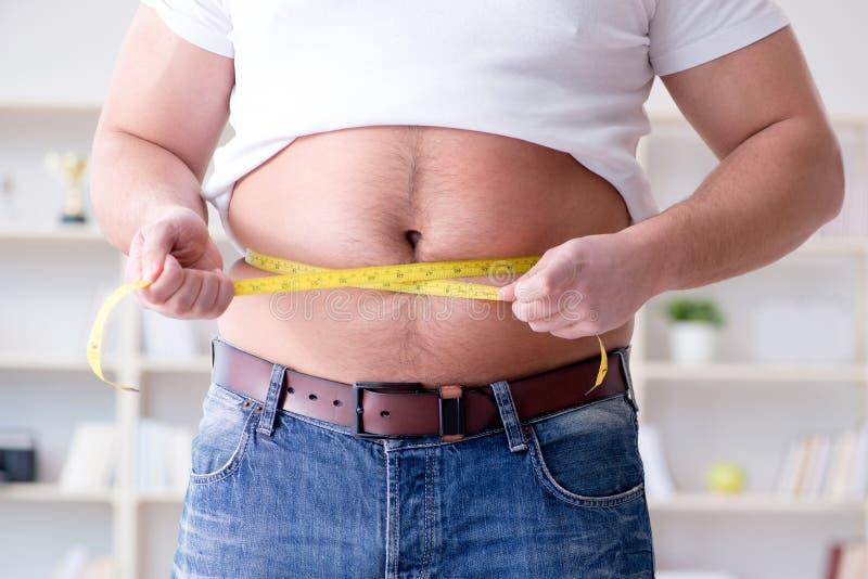 El hombre obeso gordo en concepto de dieta foto de archivo