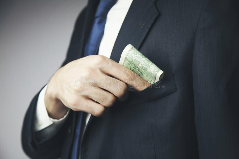 El hombre oculta un soborno en un bolsillo de su chaqueta fotografía de archivo libre de regalías