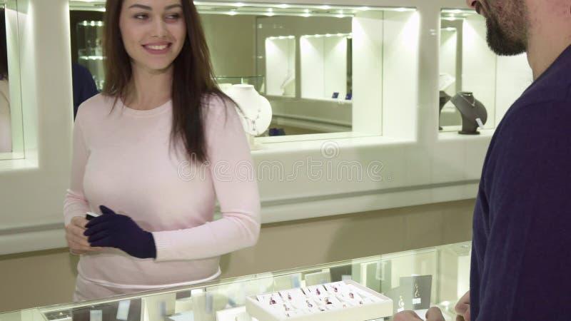 El hombre paga por la tarjeta de crédito en el boutique del jewlery foto de archivo libre de regalías