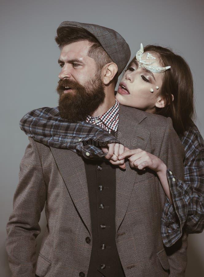 El hombre pasado de moda se vistió abrazado por la muchacha con las espinas como criatura mágica del dragón del diablo El equipo  imagen de archivo