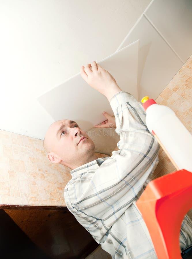 El hombre pega el azulejo del techo fotos de archivo
