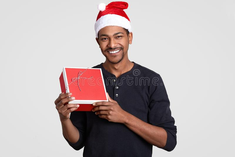 El hombre pelado oscuro positivo con la expresión alegre, pequeña barba, lleva el puente casual, lleva la caja de regalo, le cele fotografía de archivo libre de regalías