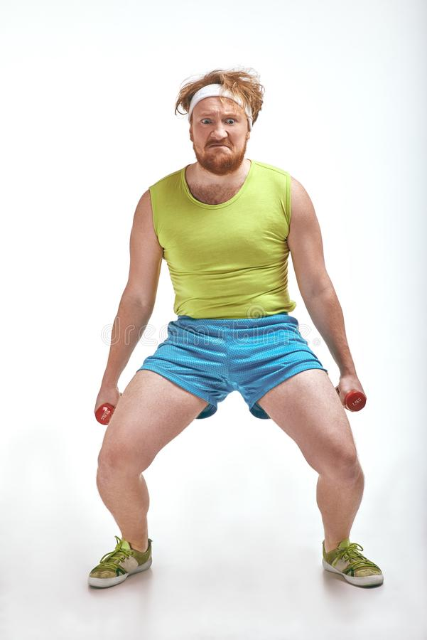 El hombre pelirrojo, barbudo, regordete está llevando a cabo las pesas de gimnasia fotos de archivo