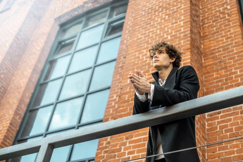 El hombre pensativo atractivo que se colocaba en escalera en rojo bricked el fondo del edificio foto de archivo libre de regalías