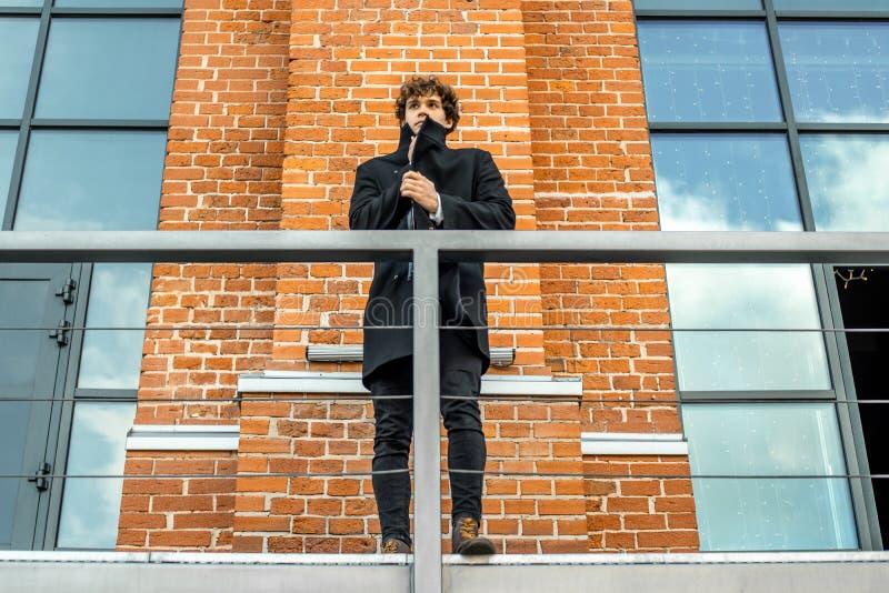 El hombre pensativo atractivo que se colocaba en escalera en rojo bricked el fondo del edificio imagen de archivo